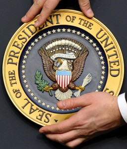 A staff fixes the presidential seal befo